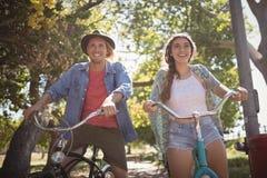 La vue d'angle faible de l'équitation heureuse de couples va à vélo Photo libre de droits