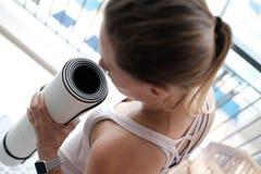 La vue d'angle supérieur au-dessus de la jeune femme un conte de poney, préparent pour une pratique en matière de yoga photos stock