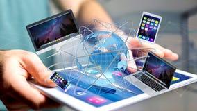 La vue d'un homme d'affaires tenant un ordinateur et des dispositifs a montré o Images libres de droits