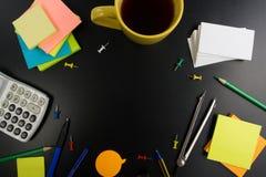 La vue de bureau de table de bureau avec l'ensemble d'approvisionnements colorés, bloc-notes vide blanc, tasse, stylo, PC, a chif Photographie stock libre de droits
