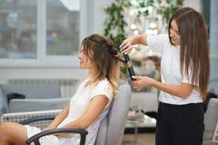 La vue de côté du coiffeur appliquant le redresseur pour faire se courbe dans le salon de beauté photos stock