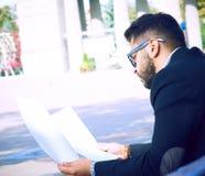 La vue de côté du jeune homme d'affaires barbu dans les vêtements sport et des lunettes étudie le document whilesitting sur un ba photos libres de droits