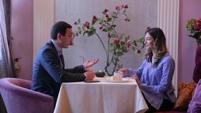La vue de côté, les couples avec du charme, l'homme dans le costume et la jolie fille de brune se reposent à la table avec la bou banque de vidéos