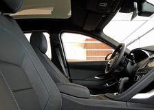La vue de côté de la position de driver's en cuir noir avec le fil a piqué l'intérieur de voiture photographie stock