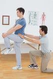La vue de côté d'un examen masculin de physiothérapeute équipe de retour Photo stock