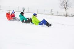 La vue de côté de jeunes amis sledging sur la neige a couvert la pente Image libre de droits