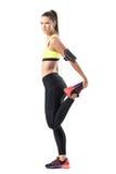 La vue de côté de l'athlète féminin étirant le quadriceps de jambe muscles tout en réchauffant Images libres de droits