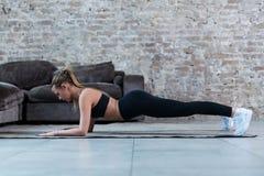 La vue de côté de l'athlète féminin mince se tenant en position de planche sur le plancher renforçant le noyau muscles à l'intéri images libres de droits
