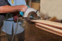 La vue de côté de la scie circulaire électrique est panneau en bois coupé contre des mains de charpentier supérieur dans l'atelie Image stock