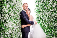 La vue de côté des ajouter romantiques de mariage aux yeux a fermé l'embrassement parmi des décorations de fleur Photographie stock