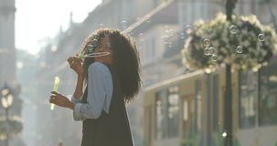 La vue de côté des bulles de savon de soufflement de fille afro-américaine avec du charme au-dessus de l'épaule L'emplacement de  banque de vidéos