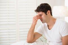 La vue de côté du jeune homme avec des yeux s'est fermée dans le lit Images stock