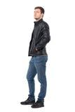 La vue de côté du jeune homme occasionnel avec des mains dans la veste en cuir empoche la recherche sérieuse Photographie stock libre de droits