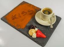 La vue de côté sur le café dans une tasse porte des fruits et le baiser de mot sur s noir Photographie stock