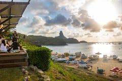 La vue de coucher du soleil du Praia font Porto avec Morro font Pico sur le fond du restaurant de Mergulhao - Fernando de Noronha Images stock