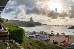 La vue de coucher du soleil du Praia font Porto avec Morro font Pico sur le fond du restaurant de Mergulhao - Fernando de Noronha Images libres de droits