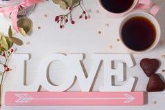 La vue de deux tasses roses de thé, le pot pour des biscuits, les biscuits sous la forme de coeur et le mot aiment Photos stock