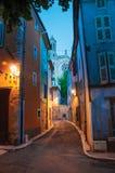 La vue de l'allée et de l'église étroites dans le début de soirée avec la lampe s'est allumée dans Rians Photographie stock libre de droits