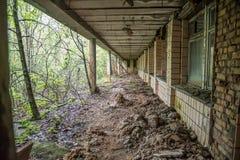 La vue de l'auvent et du désordre sous des fenêtres dans Pripyat a abandonné l'école Image libre de droits