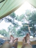 La vue de l'intérieur d'une tente à la forêt et les jambes de deux personnes émergent de la tente Photo libre de droits
