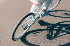 La vue de la fille arrière monte une bicyclette sur le trottoir sur un soleil Photos libres de droits