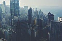 La vue de la haute à un centre d'affaires avec de hauts gratte-ciel et à la mer avec le flottement fait de la navigation de plais Photos libres de droits