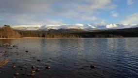 La vue de la neige a couvert le cairn Gorm et le cairn Lochan du loch Morlich Images stock