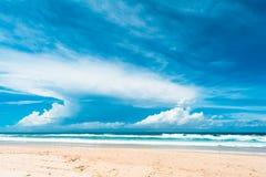 La vue de la plage d'océan avec le ciel nuageux Photographie stock