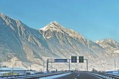 La vue de la route avec la route chante en Suisse en hiver Photos libres de droits