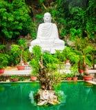La vue de la statue blanche de Bouddha et l'émeraude s'accumulent parmi les arbres verts Photo libre de droits
