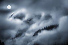 La vue de nuit du brouillard a couvert la montagne allumée par la pleine lune Image stock
