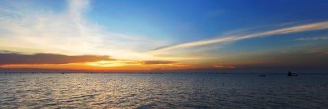 La vue de panorama du coucher du soleil orange et le ciel au-dessus de la coquille cultivent Photographie stock libre de droits
