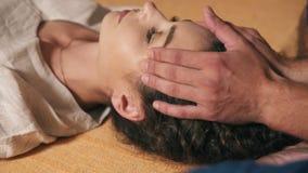 La vue de plan rapproché d'une belle fille avec ses yeux a fermé recevoir le massage thaïlandais de visage et de chef Tiré dans 4 clips vidéos