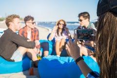 La vue de plan rapproché de la fille prend une photo du groupe d'amis sur la plage Photographie stock