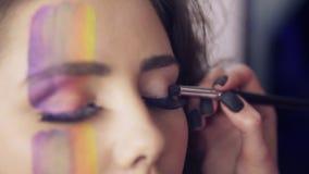 La vue de plan rapproché du maquilleur fait des modèles observer le maquillage avec les cils faux Modèle avec les mèches et l'art banque de vidéos