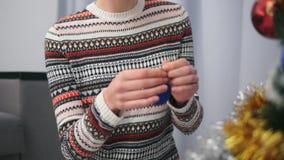 La vue de plan rapproché du ` s de femme remet décorer un arbre de Noël avec des jouets en appartement moderne Tiré dans 4k banque de vidéos