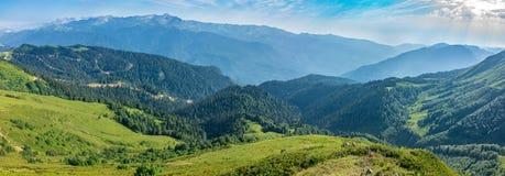 La vue de la taille de la vallée verte de montagne avec un funiculaire, entourée par de hautes montagnes Crêtes de montagne couro photo stock