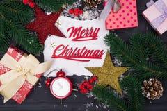 La vue des branches d'arbre de Noël, des boîte-cadeau, des horloges rouges et de Noël joue autour d'une feuille de papier blanche image libre de droits