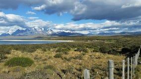 La vue des crêtes couronnées de neige de granit derrière frottent le lac bleu de champ et de saphir dans le Patagonia, Chili photo stock