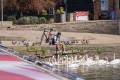 La vue du bateau de l'homme s'est reposée sur la rive entourée par des oiseaux Photographie stock libre de droits