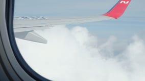 La vue du ciel bleu et des nuages par la fenêtre des avions, se ferment vers le haut de la fenêtre d'avion avec l'aile d'avion banque de vidéos