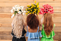 La vue du dos de trois femmes tenant des bouquets fleurit Photo libre de droits
