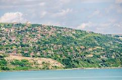 La vue du rivage de la Mer Noire, collines vertes avec des maisons, bleu opacifie le ciel Côte de Balchik de ville, eau de mer bl Photos libres de droits