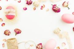 La vue du rose de Pâques eggs avec la ficelle, les fleurs et les bandes sur le fond blanc, vue supérieure, configuration de grais Photographie stock
