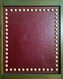 La vue en bois carrée avec le cuir et le groupe rouges de luxe de métal d'or se boutonne avec l'espace de copie sur le cuir rouge Image stock