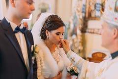 La vue en gros plan de la belle jeune mariée embrassant l'anneau de mariage Images stock