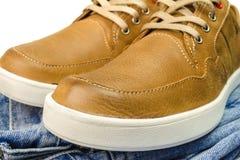 La vue en gros plan de couleur bronzage, les espadrilles en cuir sur des jeans halètent Images libres de droits
