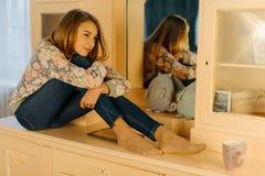 La vue en gros plan de l'adolescente de sourire étreignant les genoux et s'asseyant sur la raboteuse Photos stock
