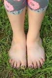 La vue en gros plan de la petite fille déchaussée botte avec la pointe du pied sur des pieds Photo stock