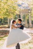 La vue en gros plan du marié portant la jeune mariée au fond du parc photographie stock